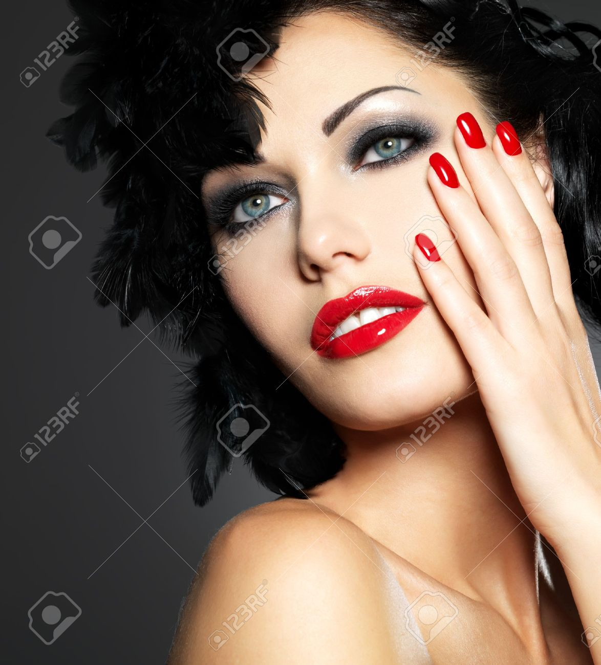 Beautiful fashion woman with red nails, creative hairstyle and makeup - Model posing in studio Stock Photo - 16732157
