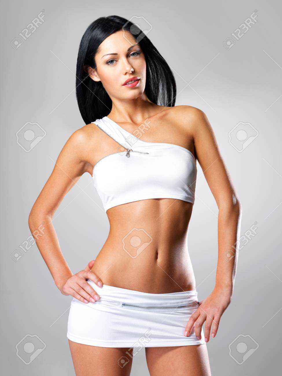Pretty woman with beautiful slim tanned body - posing at studio on gray background Stock Photo - 16642962