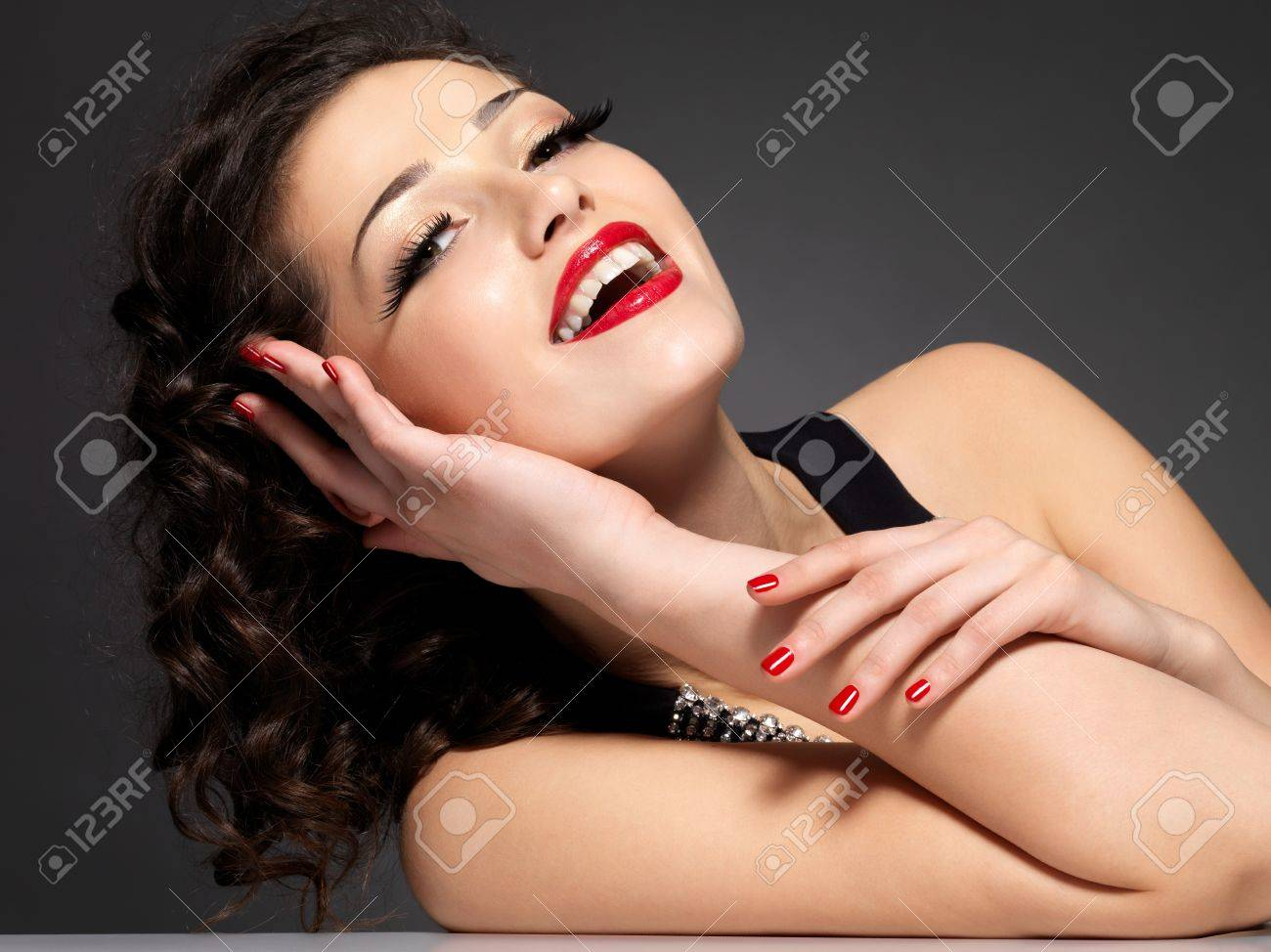 Young pretty woman with red manicure and  lips.  Fashion model with bright positive emotions Stock Photo - 16858855
