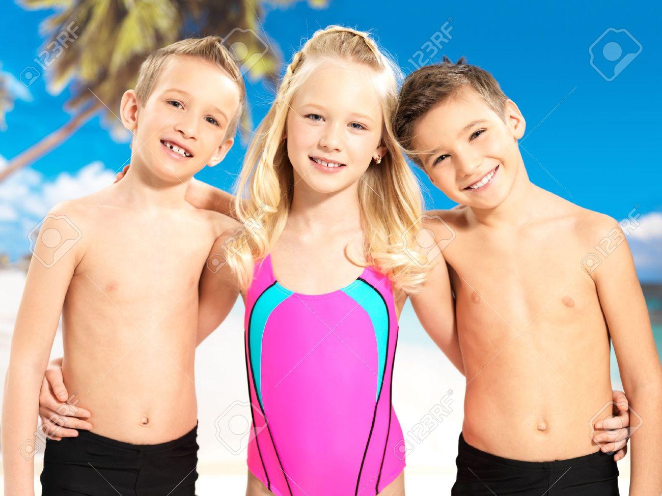 archivio fotografico ritratto dei bambini felici che godono in spiaggia bambini scolaro in piedi insieme in costume da bagno di colore luminoso