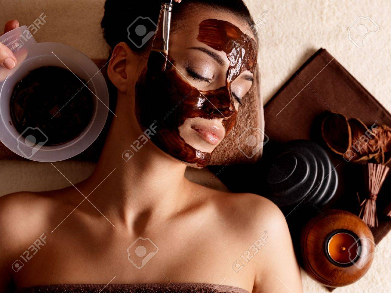 Spa therapy for young woman receving cosmetic mask at beauty salon - indoors Stock Photo - 17642644