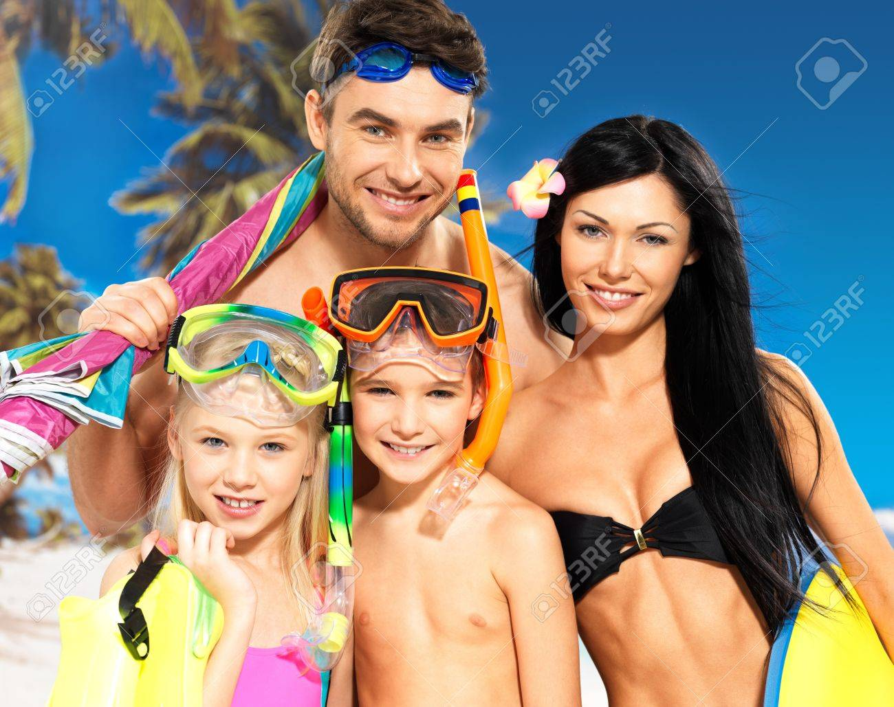 Portrait of  happy fun beautiful family with two children at tropical beach with protective swimming mask Stock Photo - 18352260
