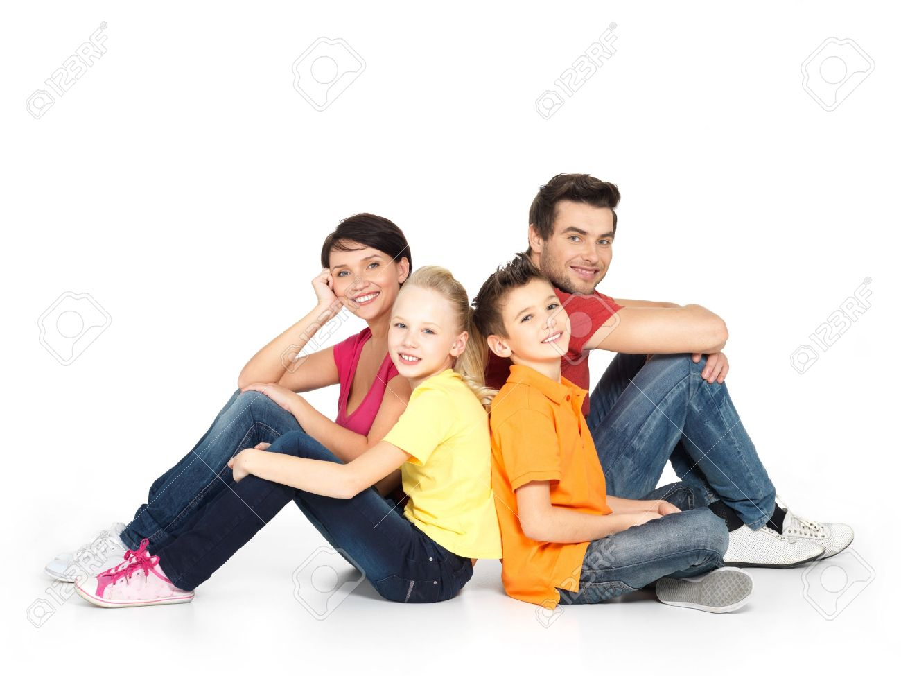 Portrait of the happy  family with two children sitting at studio on white floor Stock Photo - 18629060