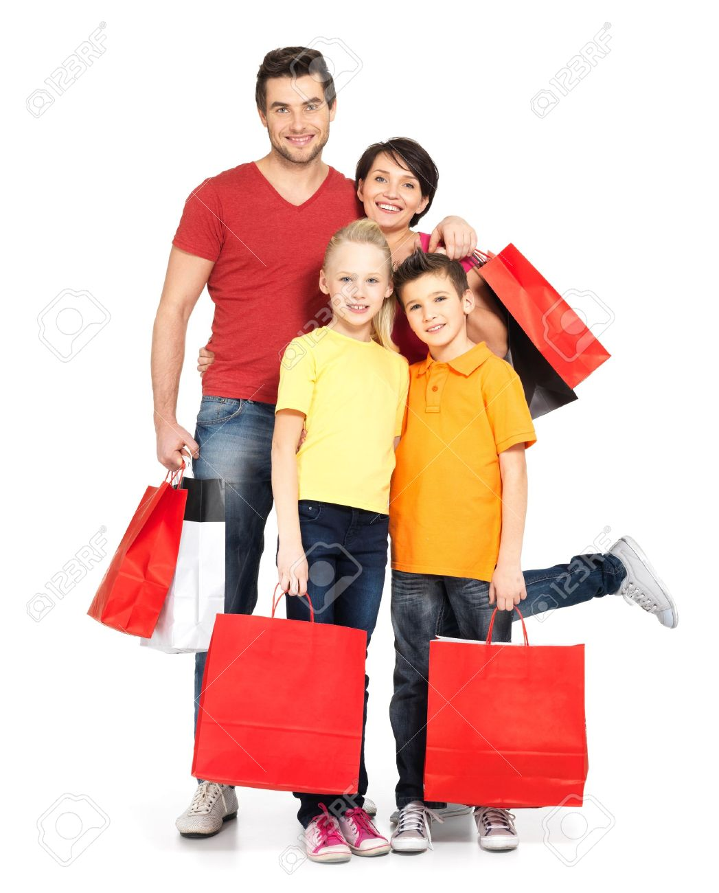 Happy Family With Shopping Bags Standing At Studio Over White ...