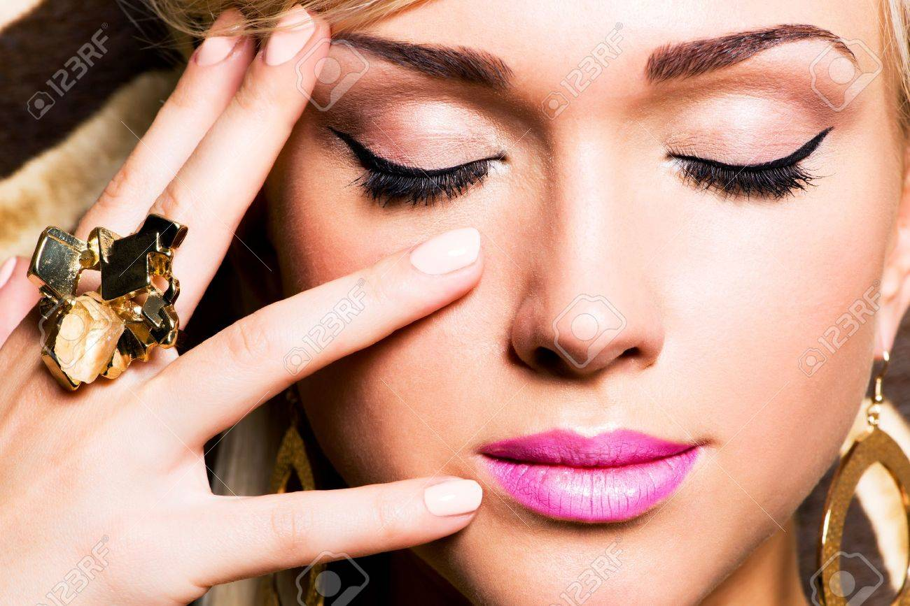Closeup portrait of beautiful face of sexy woman with fashion makeup and gold ring on finger Stock Photo - 18856291