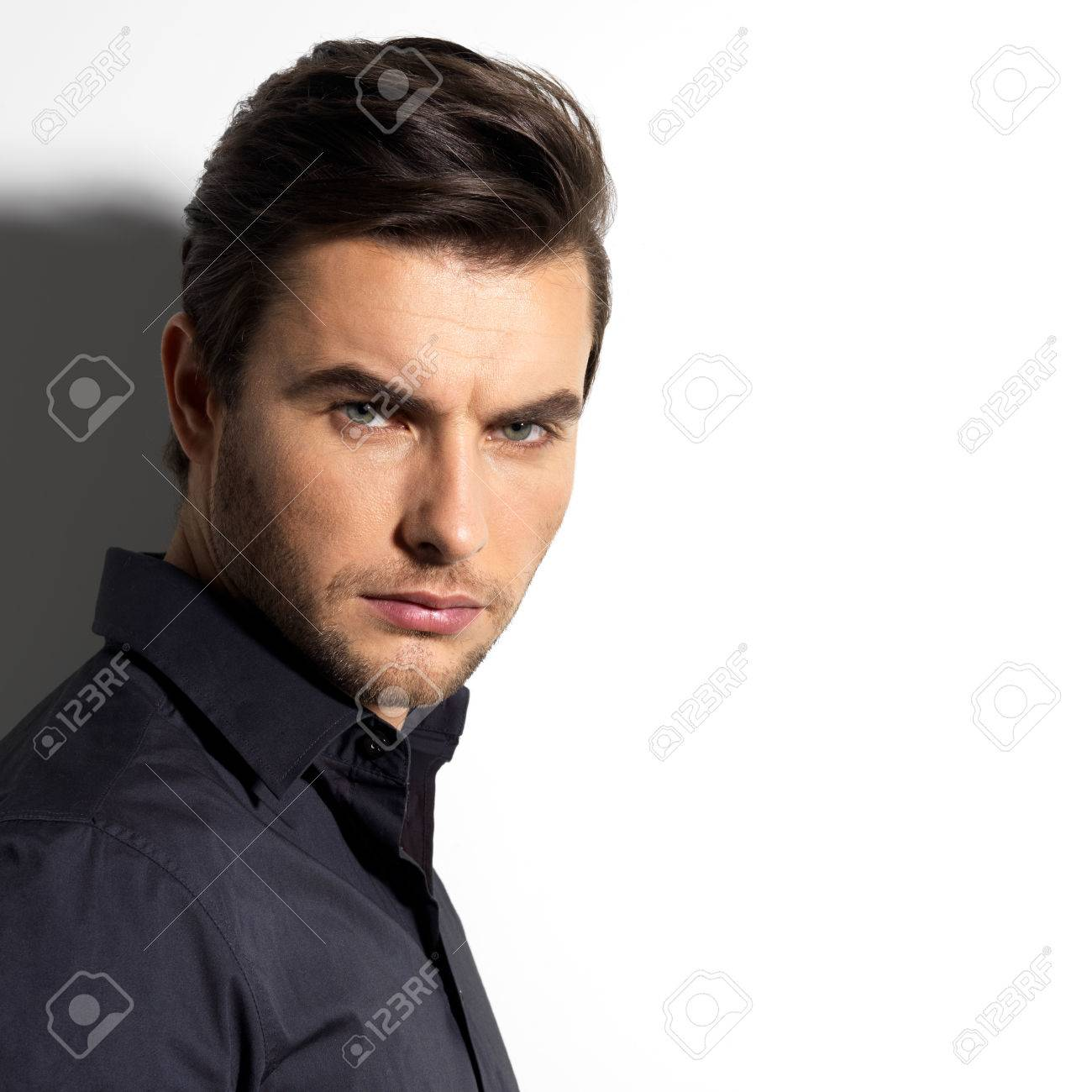 Fashion portrait of young man in black shirt poses over wall with contrast shadows Stock Photo - 23190293