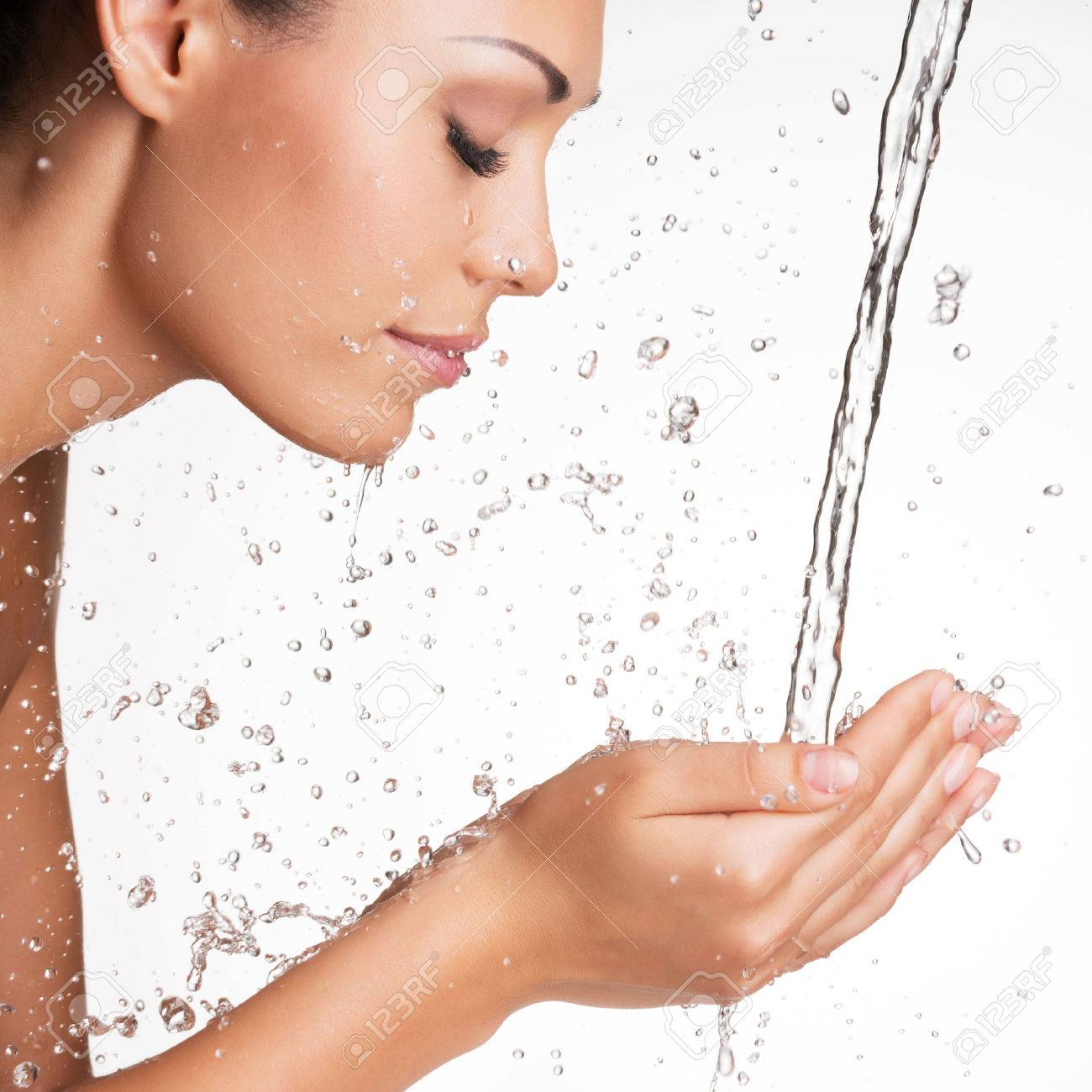 Closeup portrait of a beautiful woman washing her clean face with water Stock Photo - 23233454