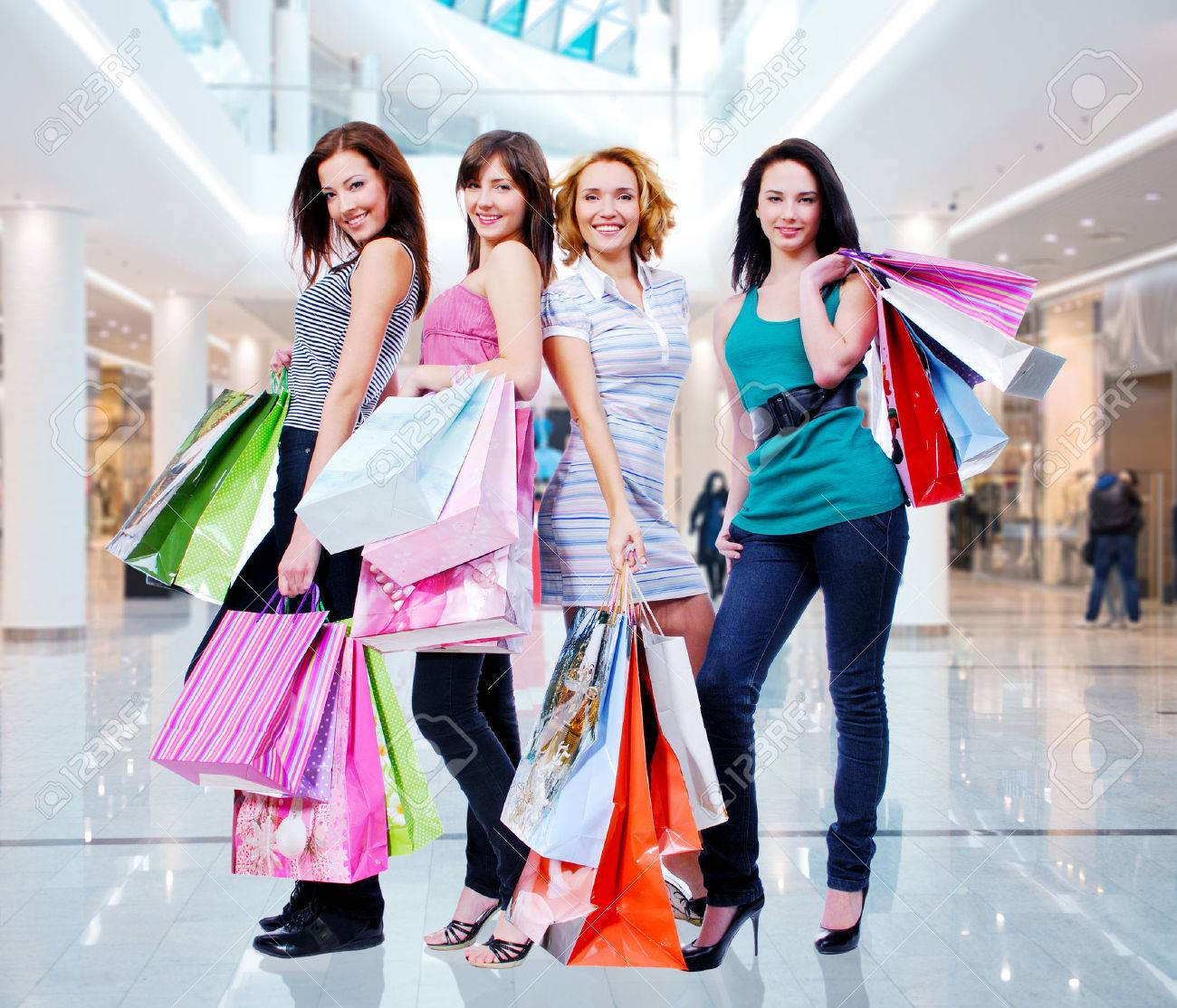Happy beautiful women with shopping bags stands at shop Stock Photo - 22997105