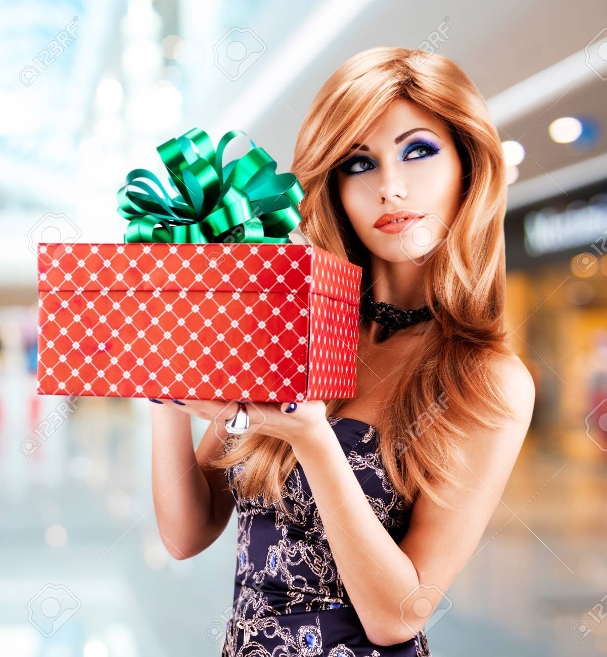Bautiful Woman Holds The Birthday Gift Red Box With Green Ribbon