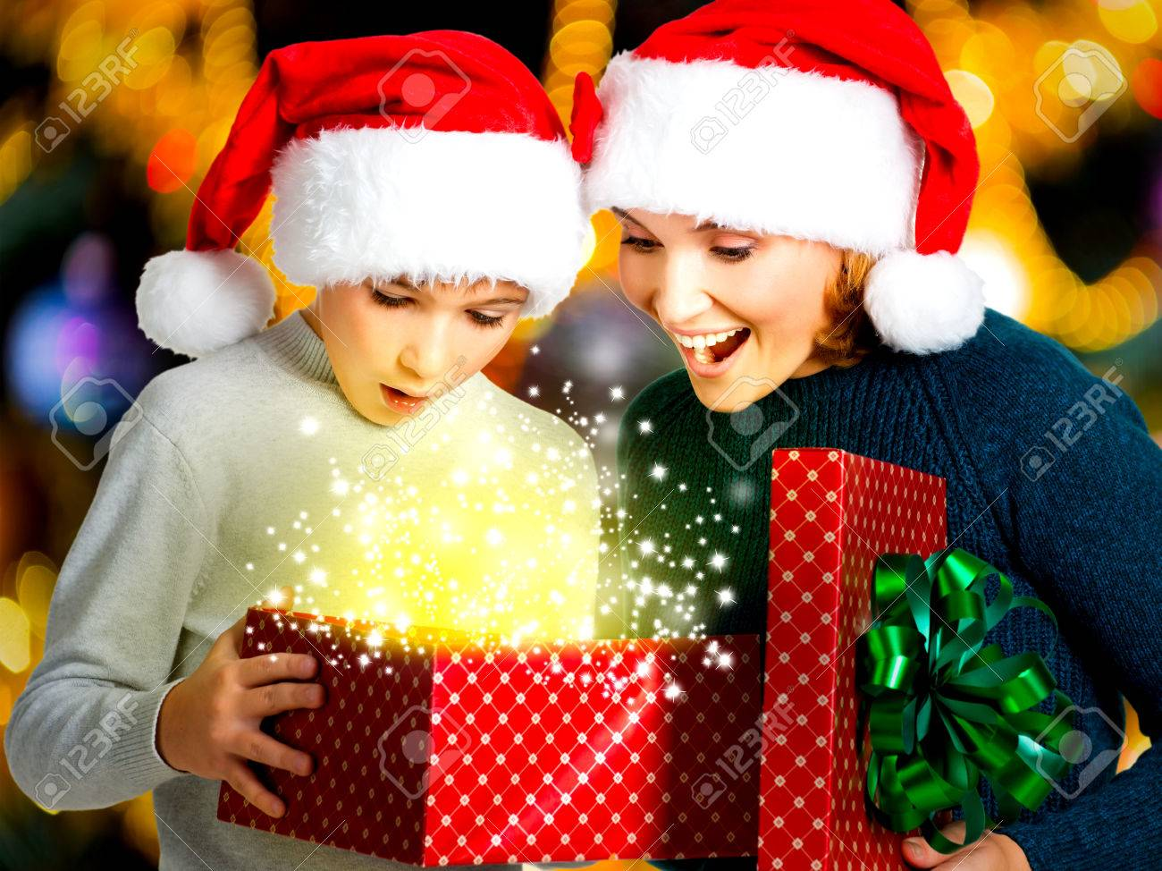 Young mother with  child opens the box with gifts on the christmas holiday - indoors Stock Photo - 23233593