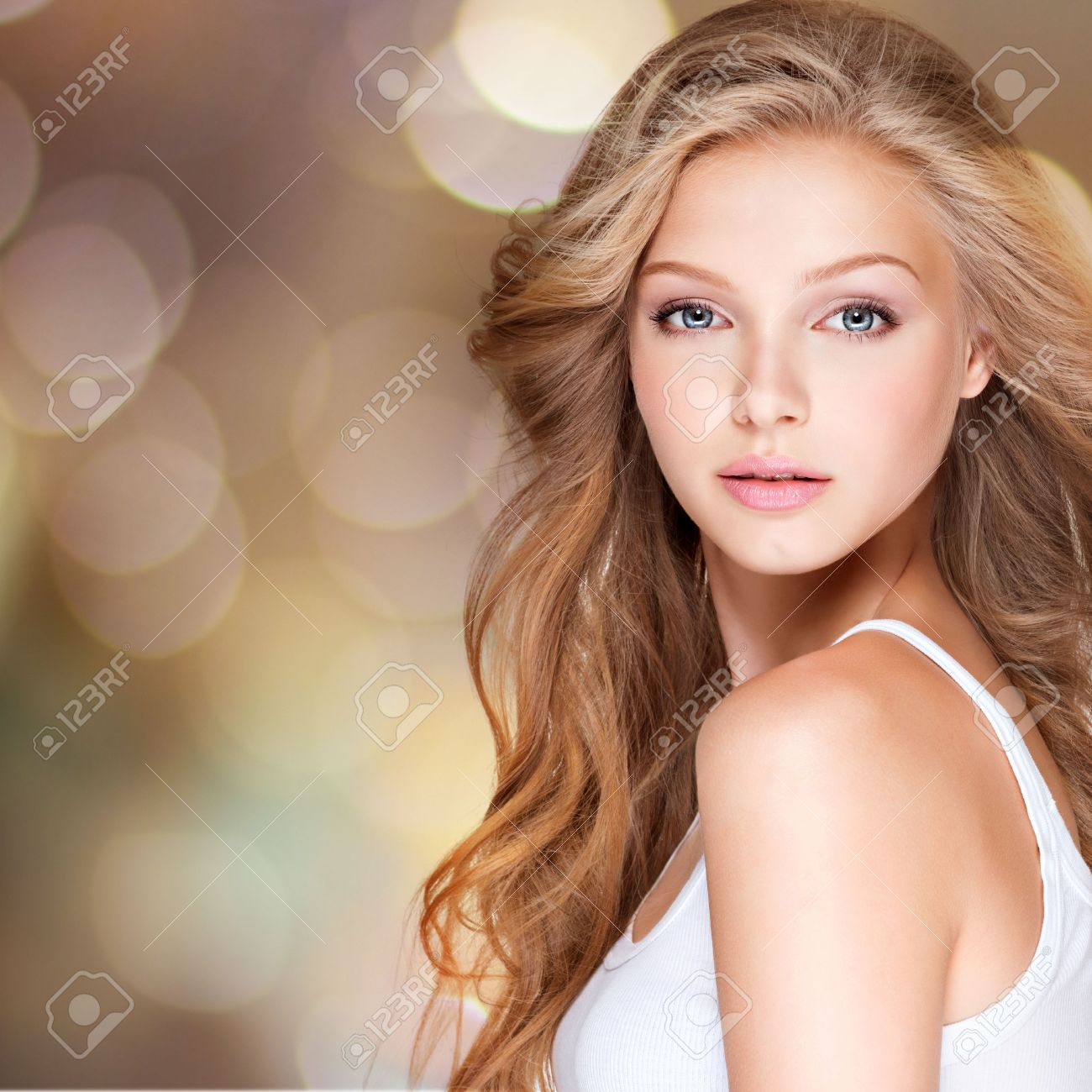 Portrait of beautiful  young woman with long curly hair. Closeup face of a pretty caucasian model looking at camera Stock Photo - 33624703