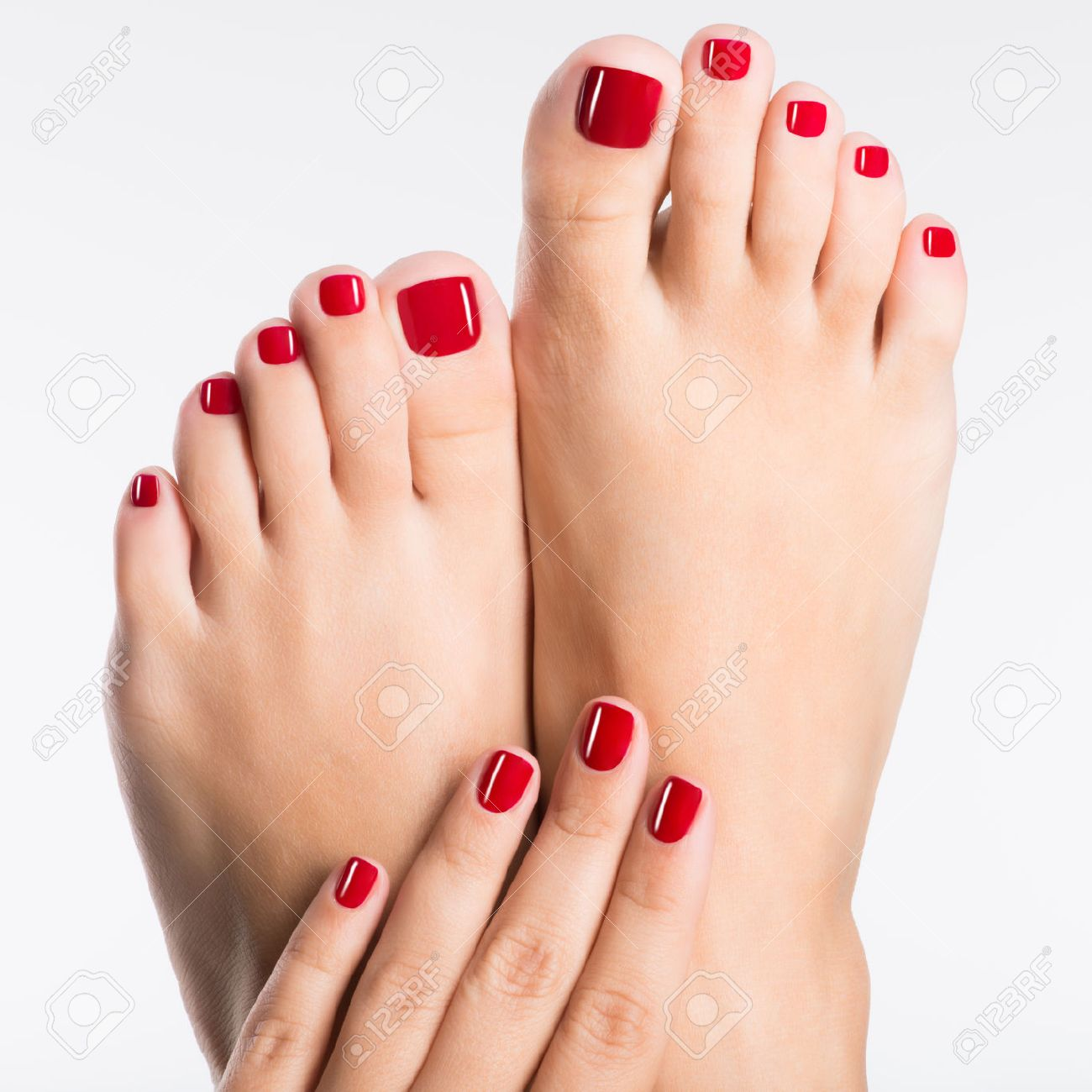 Closeup photo of a female feet with beautiful red pedicure over white background - 53558712