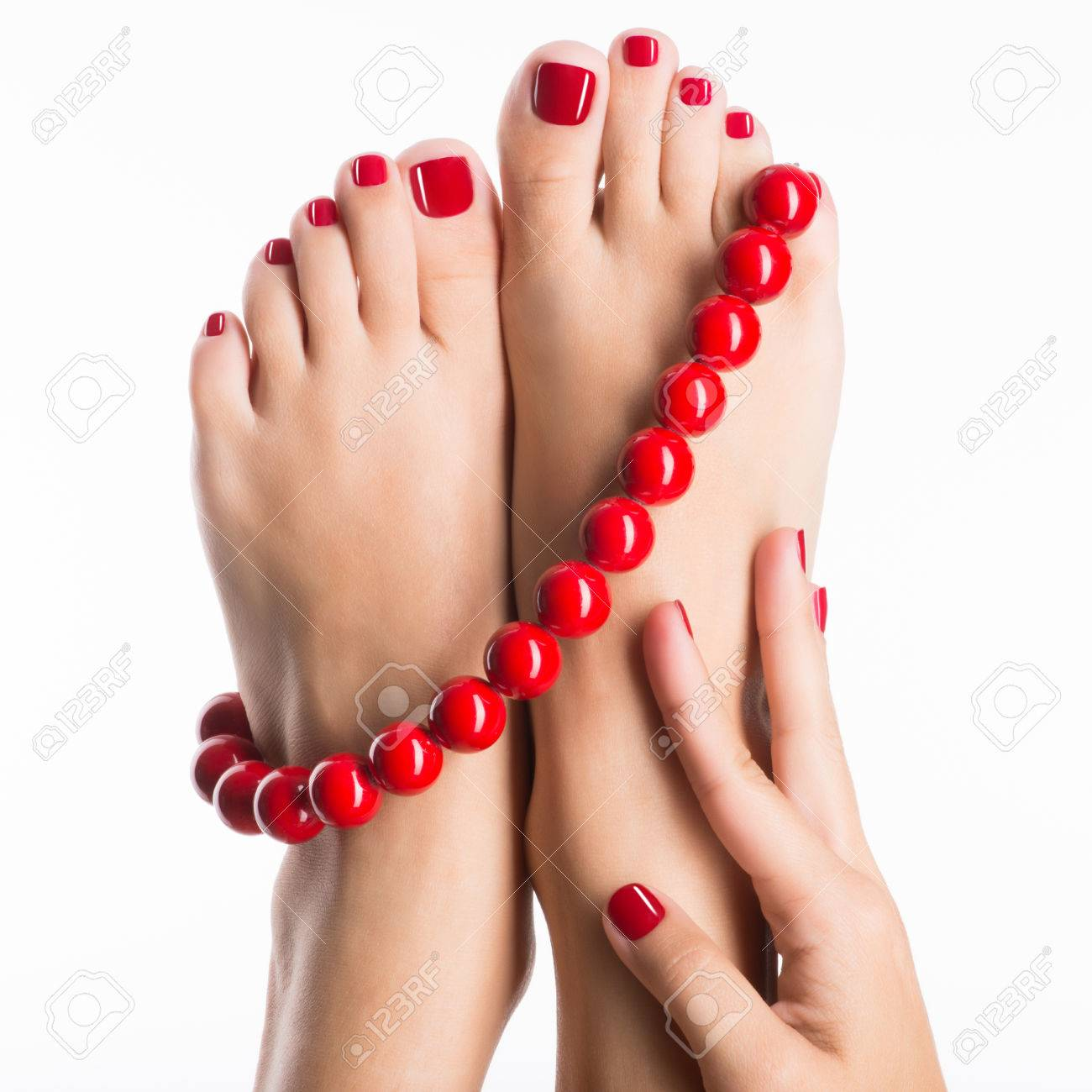 Closeup photo of a female feet with beautiful red pedicure and big beads -  over white background Banque d'images - 53558740