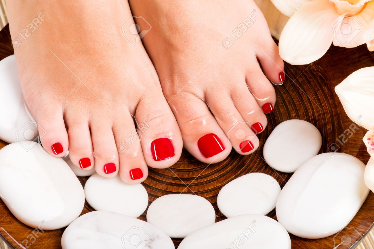 Closeup photo of a beautiful female feet with red pedicure Banque d'images - 53558850