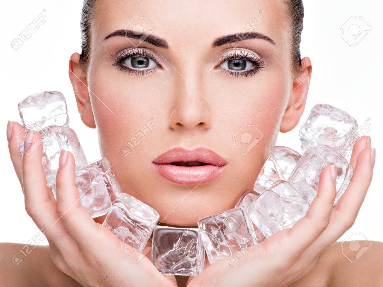 Beautiful young woman applies the ice to face. Skin care concept. Banque d'images - 53559271