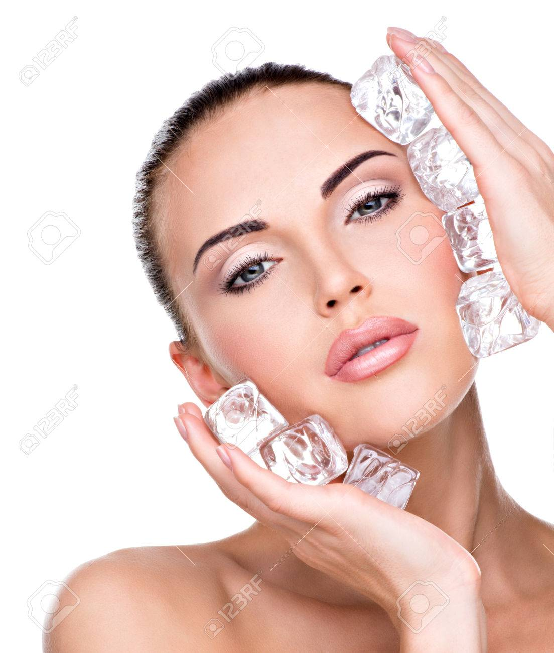 Beautiful young woman applies the ice to face. Skin care concept. - 53559274