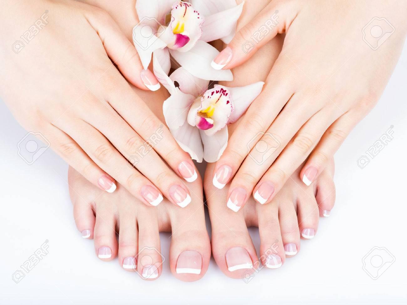 Closeup photo of a female feet at spa salon on pedicure and manicure procedure - Soft focus image - 54100907