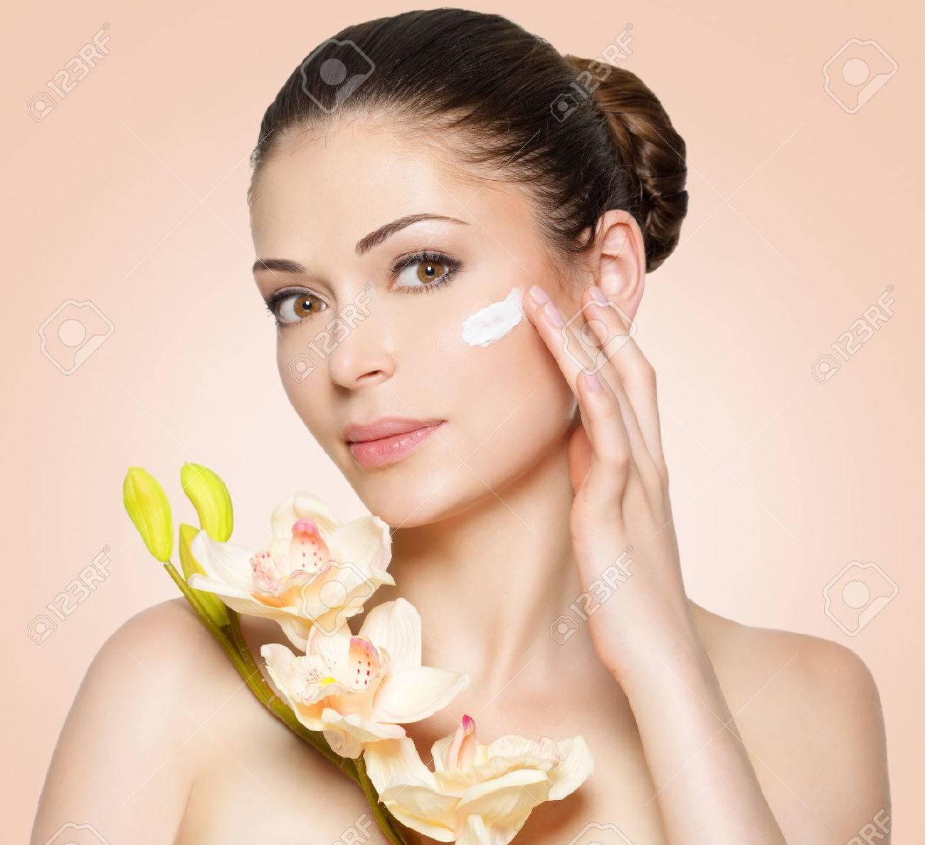 Jeune femme avec crème cosmétique sur un visage propre et fraîche. concept de mode de vie sain Banque d'images - 54105411
