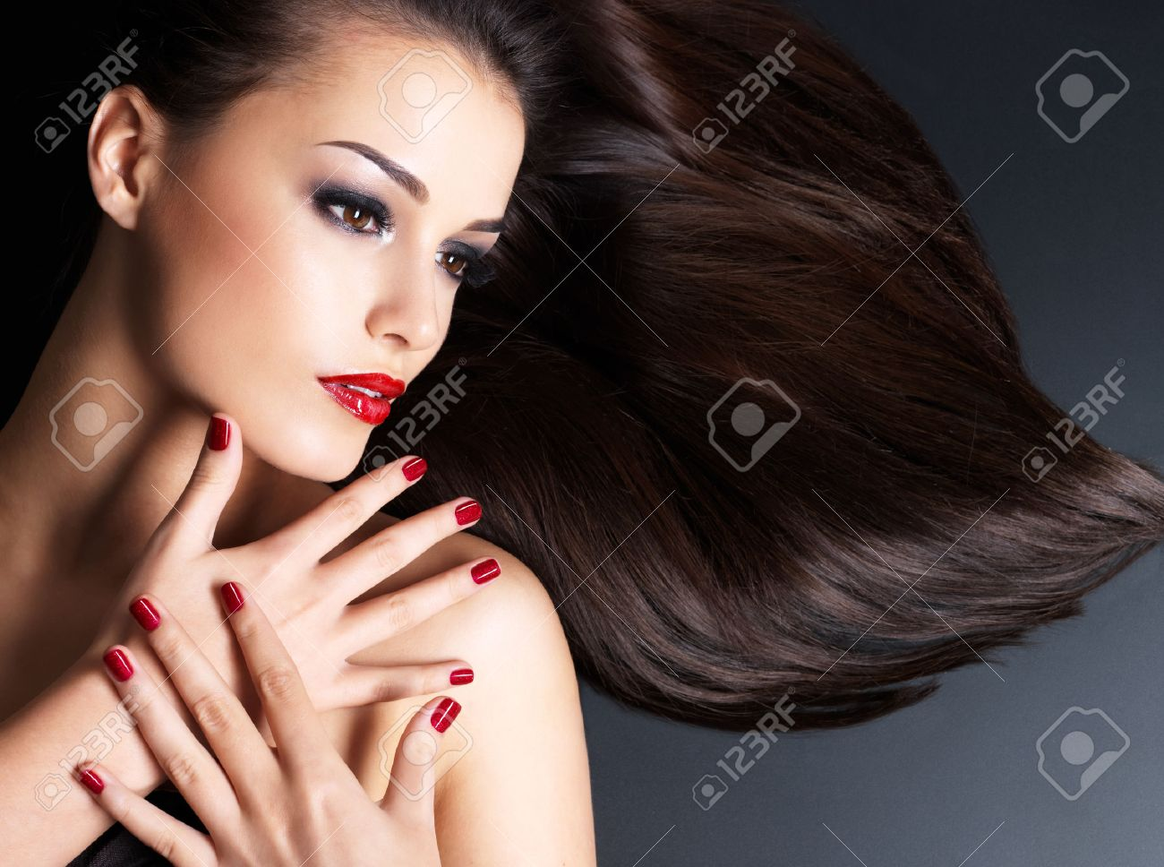 Beautiful woman with long brown straight hairs and red nails lying on the dark background Banque d'images - 54106516