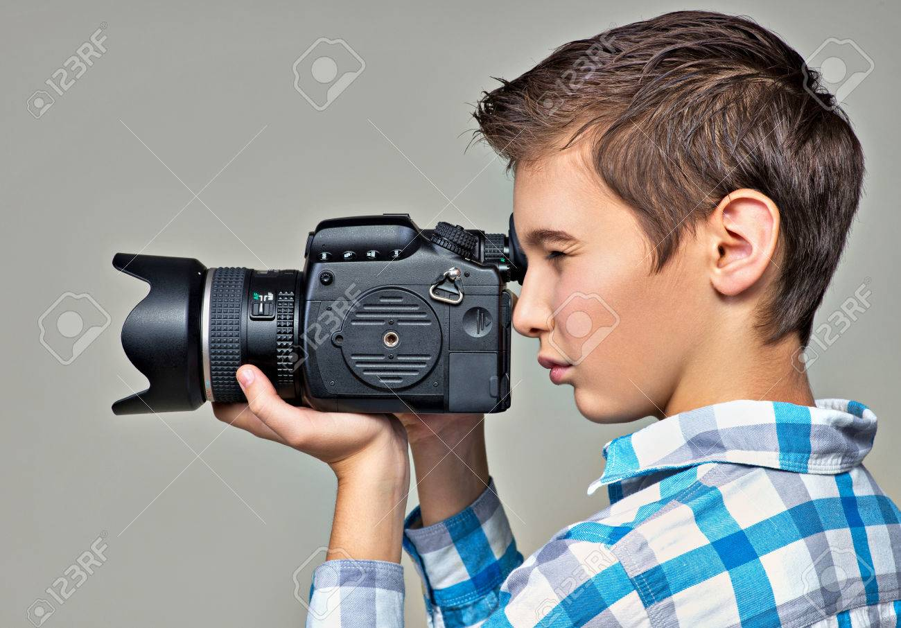 Stock Photo - Teen boy with dslr camera photographing. Boy with camera  taking pictures. Profile portrait.