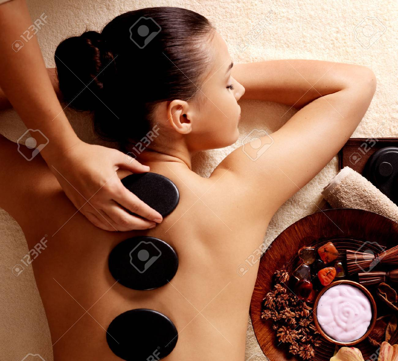 Young woman getting hot stone massage in spa salon. Beauty treatment concept. Banque d'images - 62833668