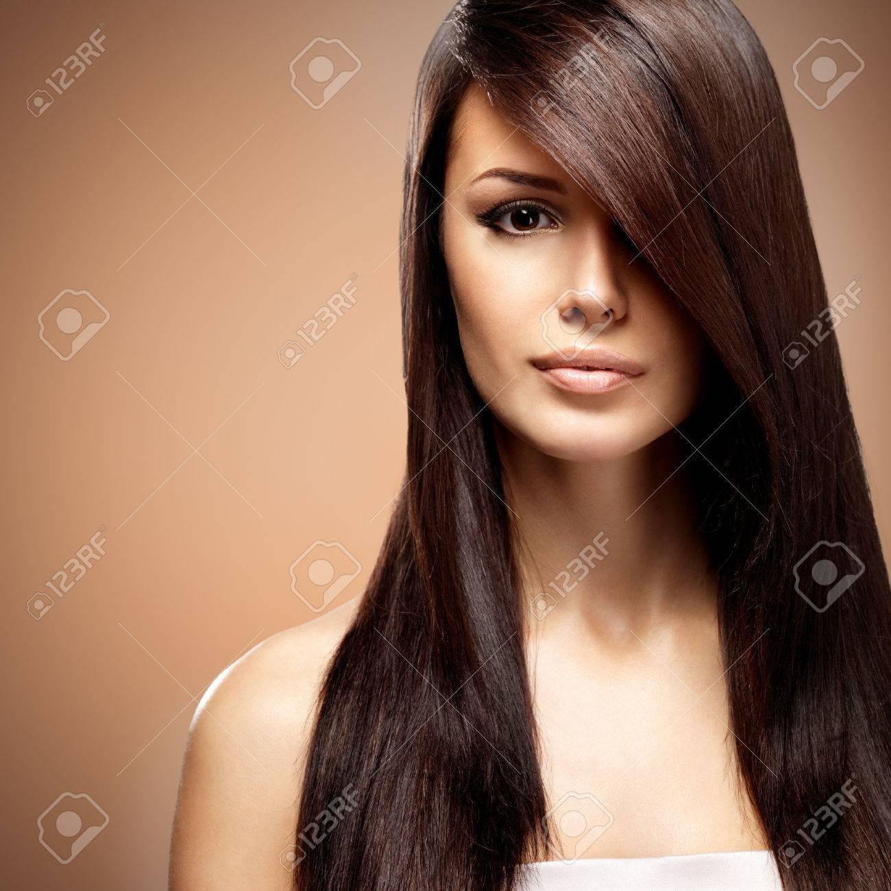 Belle jeune femme avec de longs cheveux bruns raides. Fashion model pose au studio sur fond beige Banque d'images - 63432208
