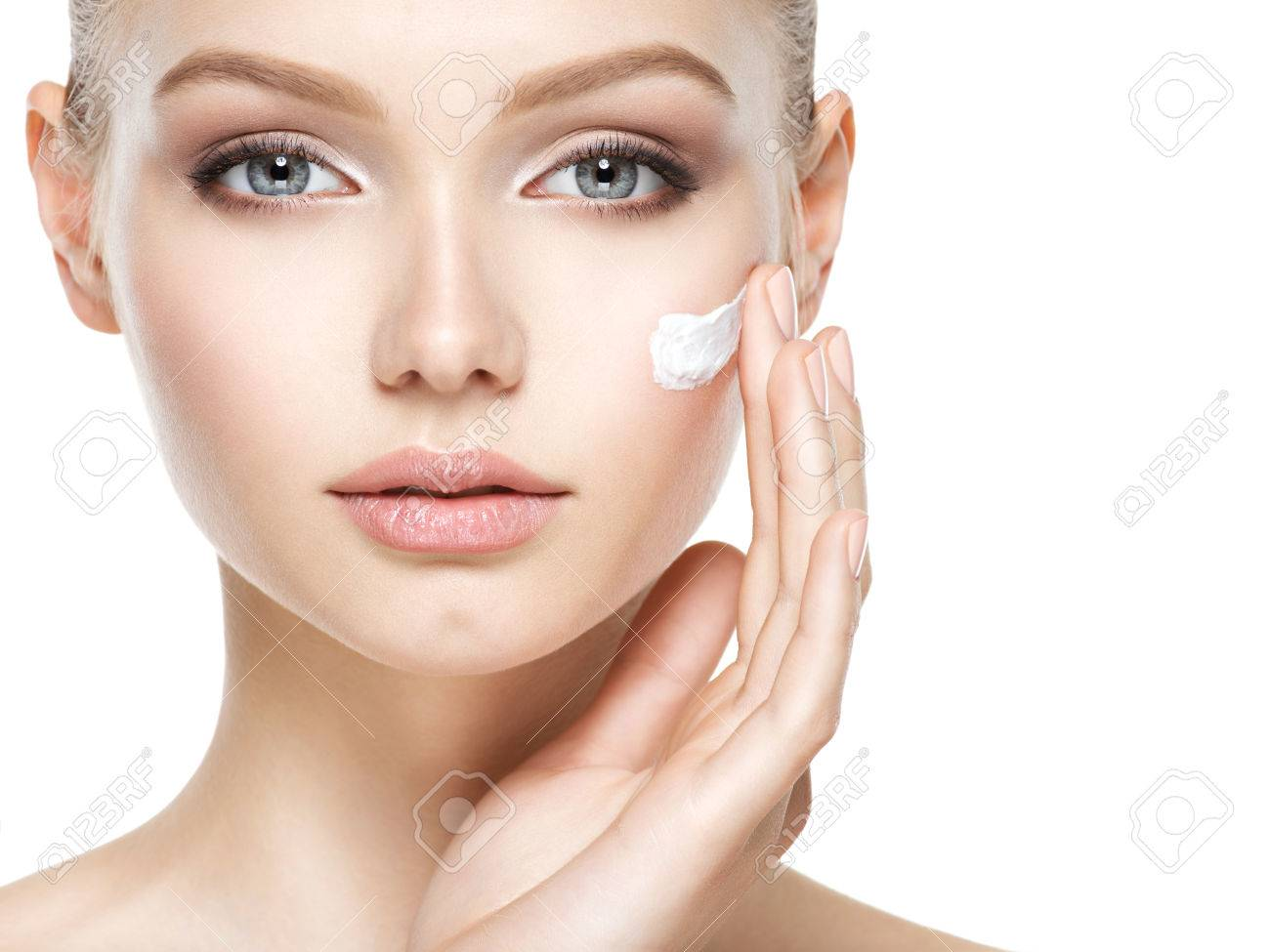 Young woman with cosmetic  cream on a clean fresh face Banque d'images - 63650649