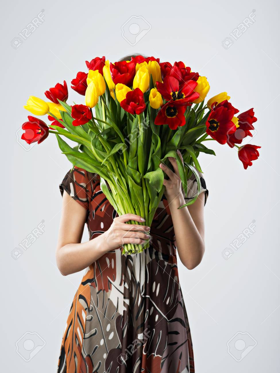 Girl Covering Her Face With Big Bouquets Of Flowers Stock Photo