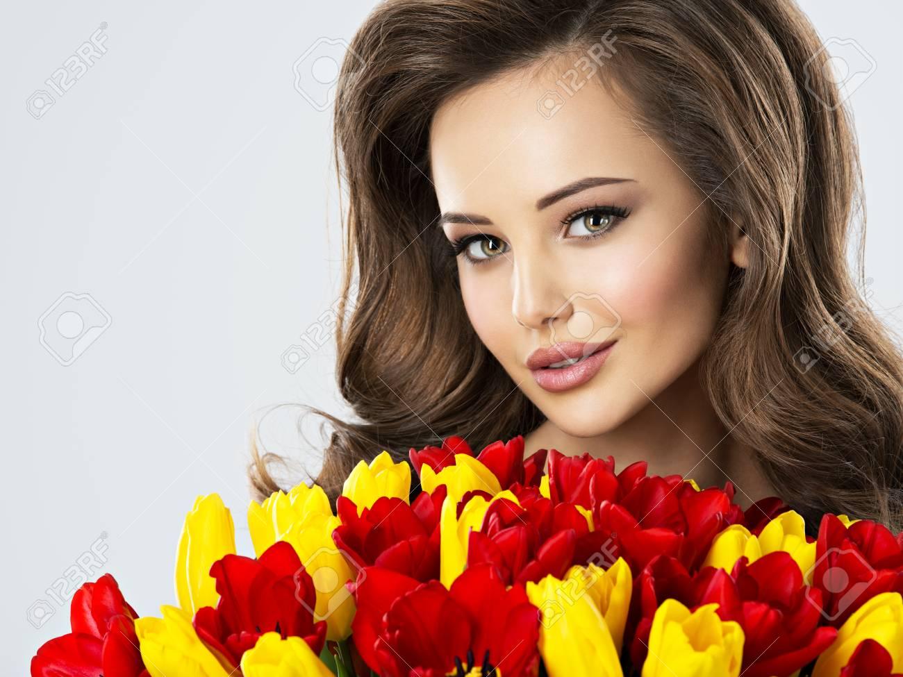 Beautiful young woman with flowers pretty girl holds the red beautiful young woman with flowers pretty girl holds the red tulips closeup portrait stock izmirmasajfo