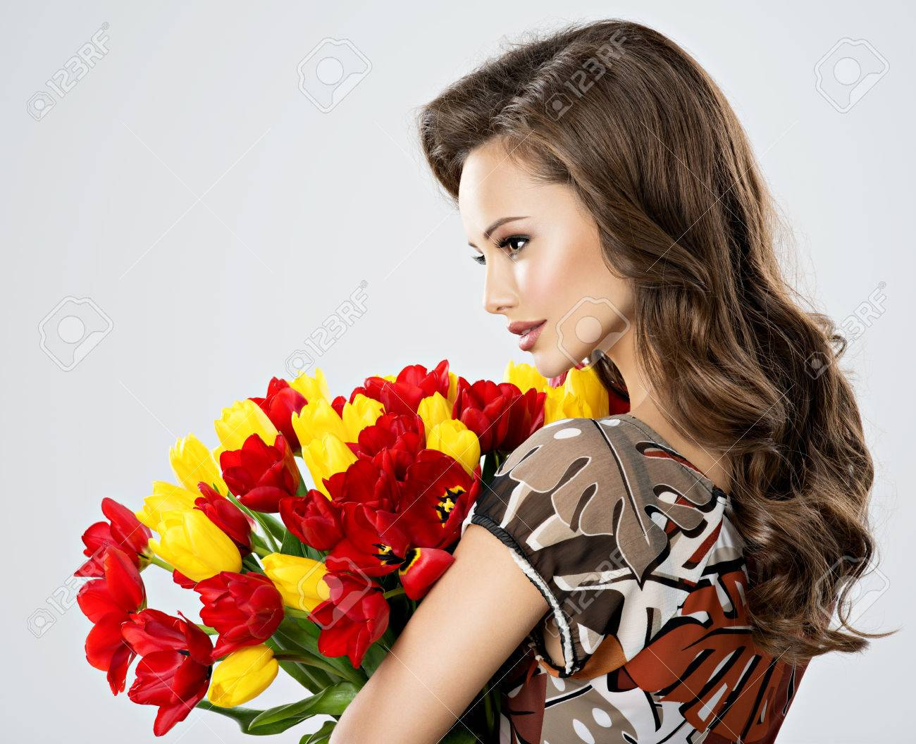 Beautiful young woman with flowers in hands pretty girl holds beautiful young woman with flowers in hands pretty girl holds the red tulips profile izmirmasajfo