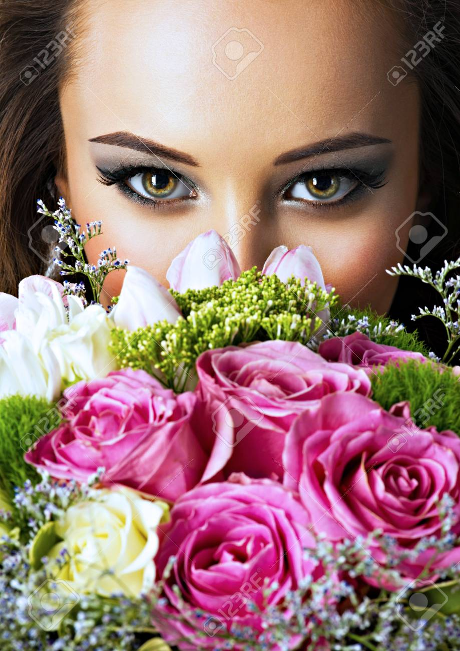 Closeup face of beautiful girl with flowers young attractive closeup face of beautiful girl with flowers young attractive woman holds the bouquet of spring izmirmasajfo