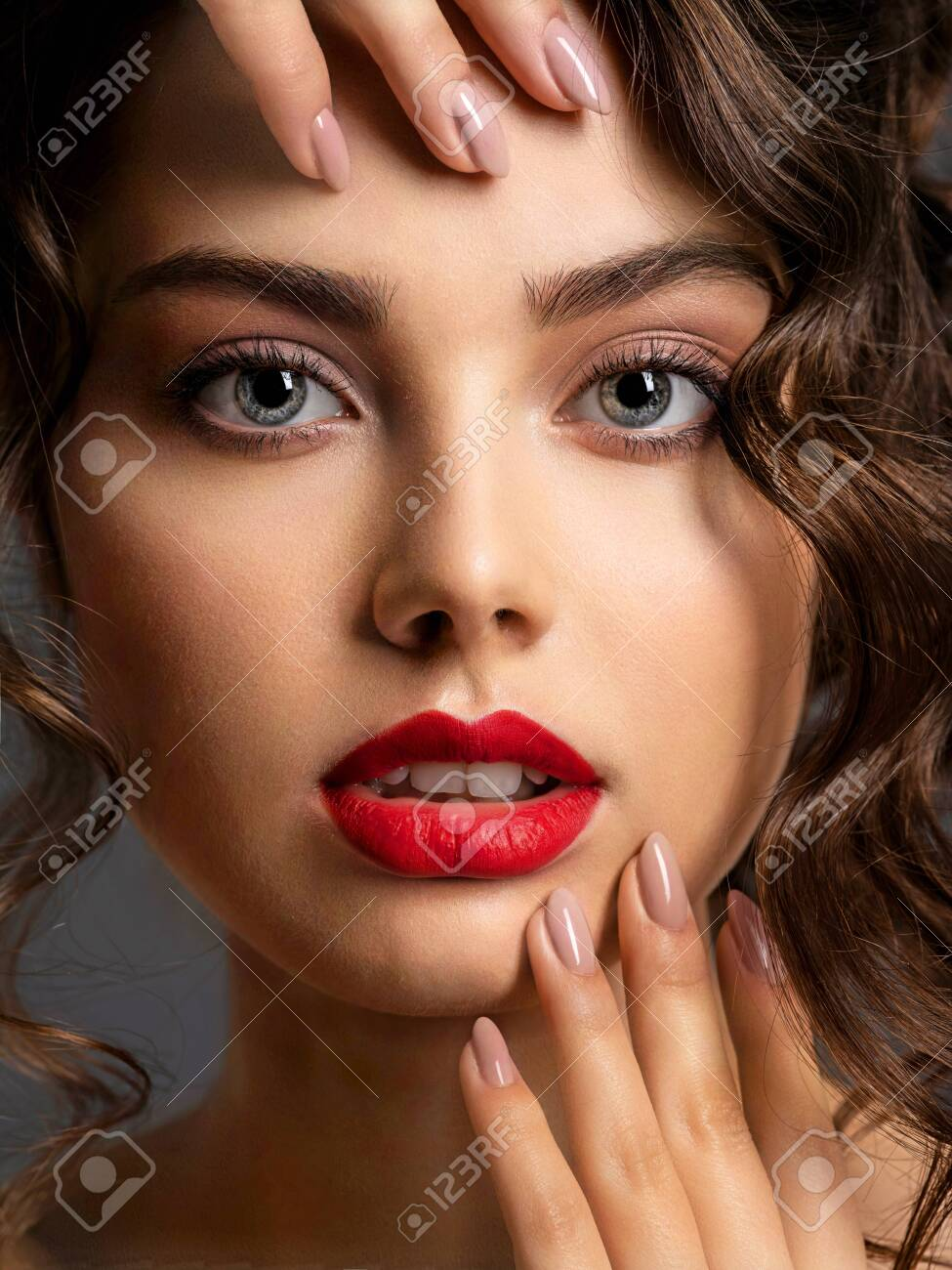 Closeup Face of a beautiful woman with a smoky eye makeup and red lipstick. Sexy brunette girl with long curly hair. Portrait of an attractive female - at studio. Fashion model. Beautiful eyes. - 122585551
