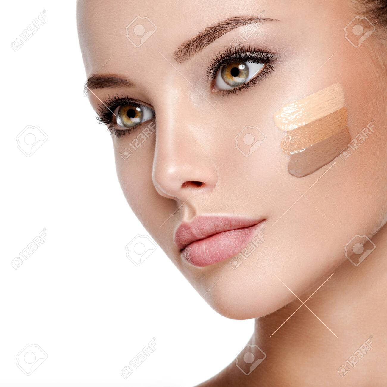 Beautiful face of young woman with cosmetic foundation on a skin. Beauty treatment concept - 129438385