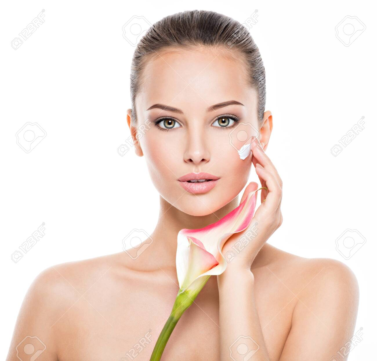 Woman applying cosmetic cream on a face. Fresh flower on the body - 130478540