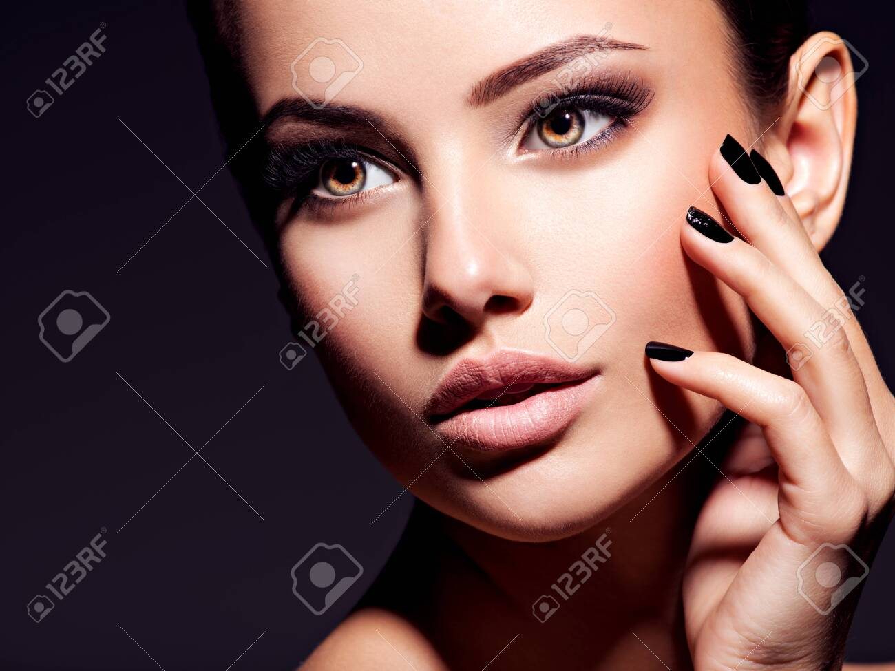 Face of a beautiful girl with fashion makeup and black nails posing at studio over dark background - 139477244