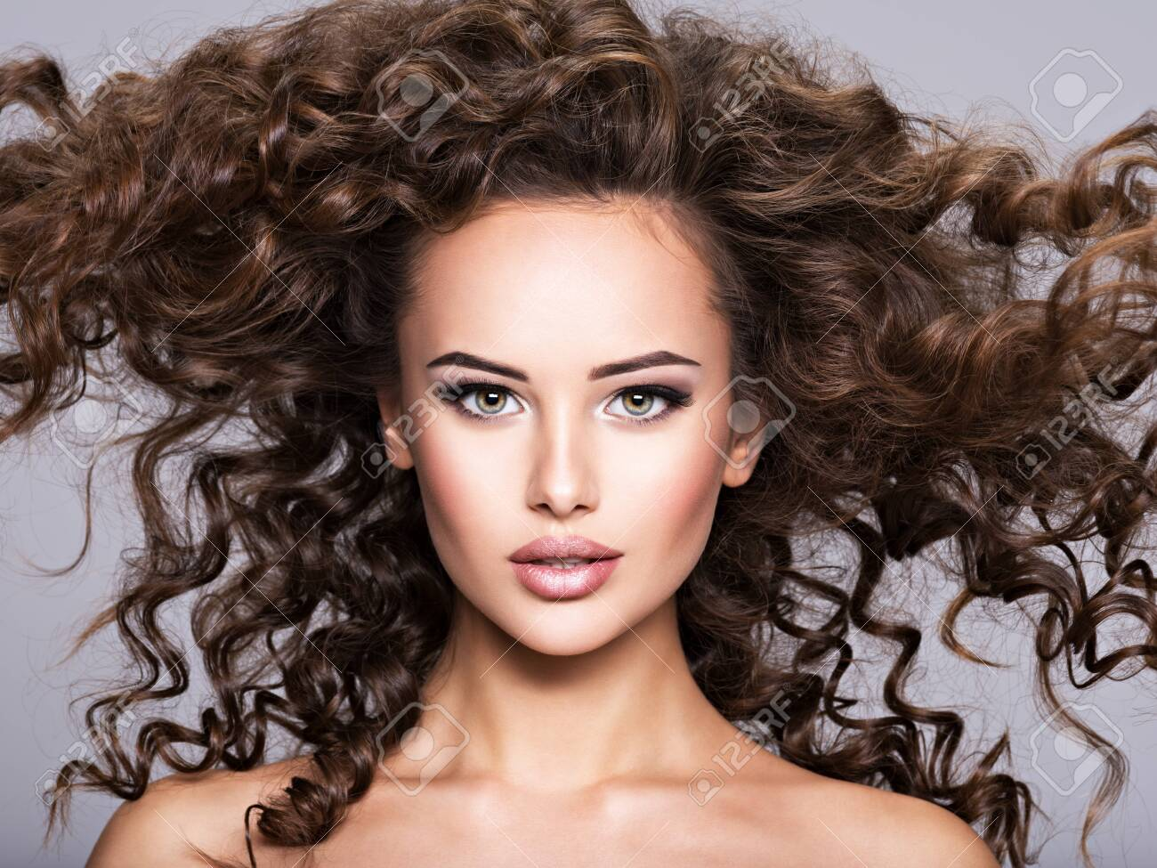 woman with long bown curly hair. Portrait of a Beautiful Brunette girl with long hair - 139477250