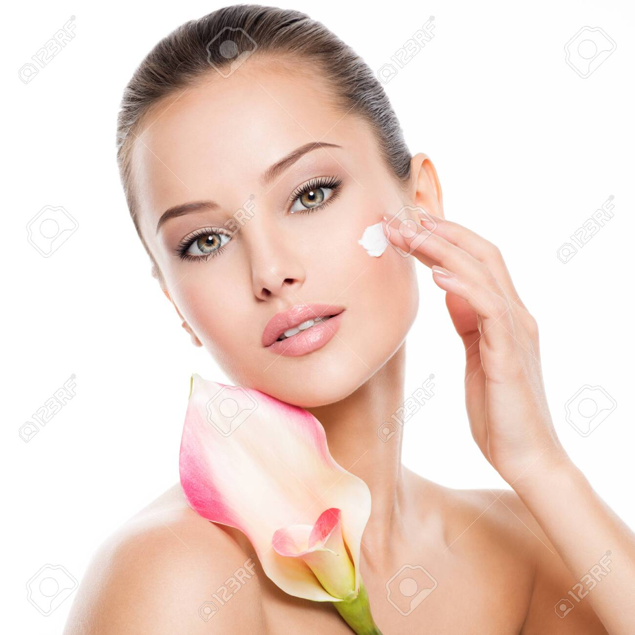 Woman applying cosmetic cream on a face. Fresh flower on the body - 139390557