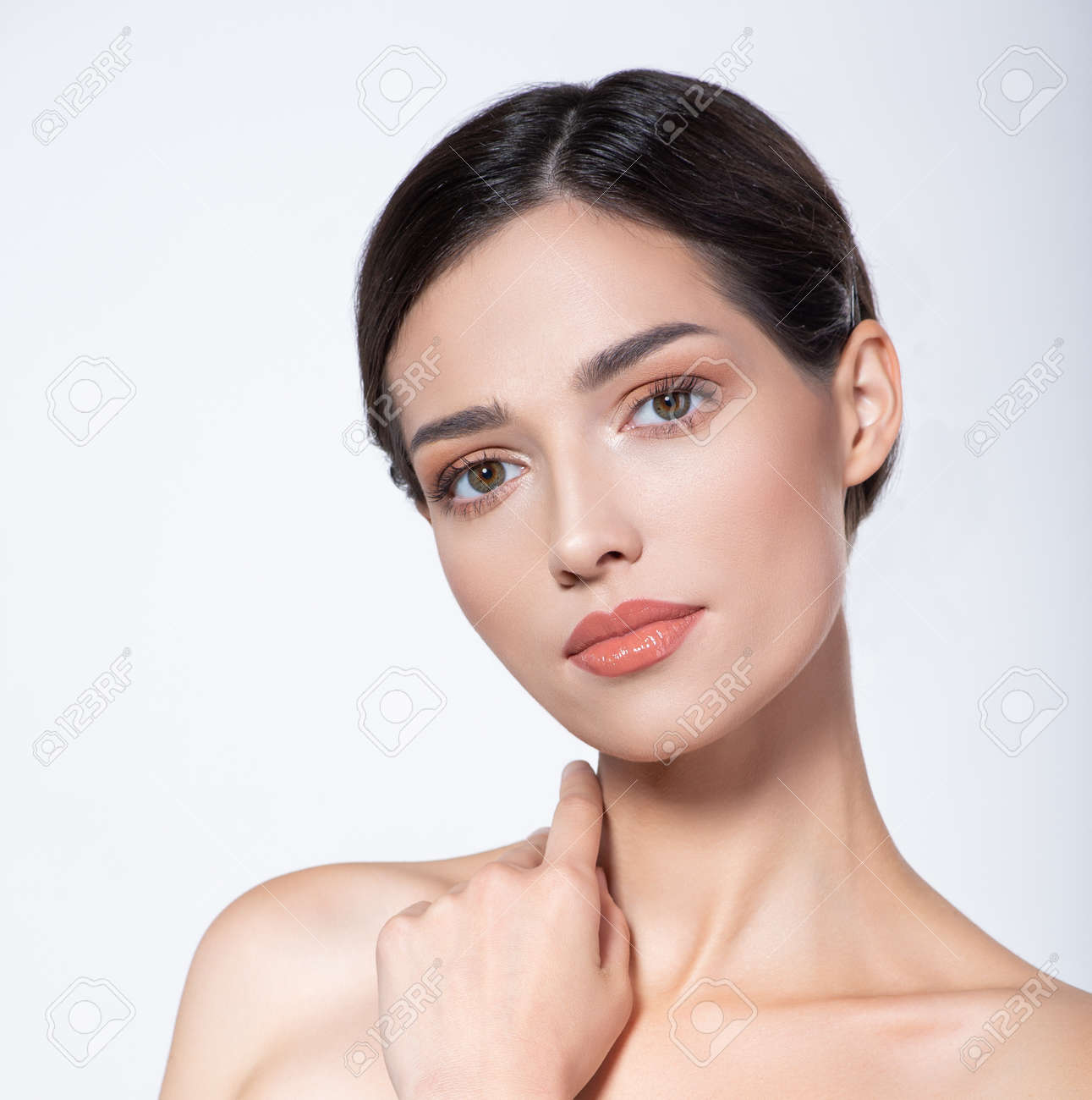 Portrait of beautiful brunette girl which touching her fresh face. Beautiful face of young woman with health fresh skin. Beautiful face of young adult woman with clean fresh skin. Skin care. - 155077014
