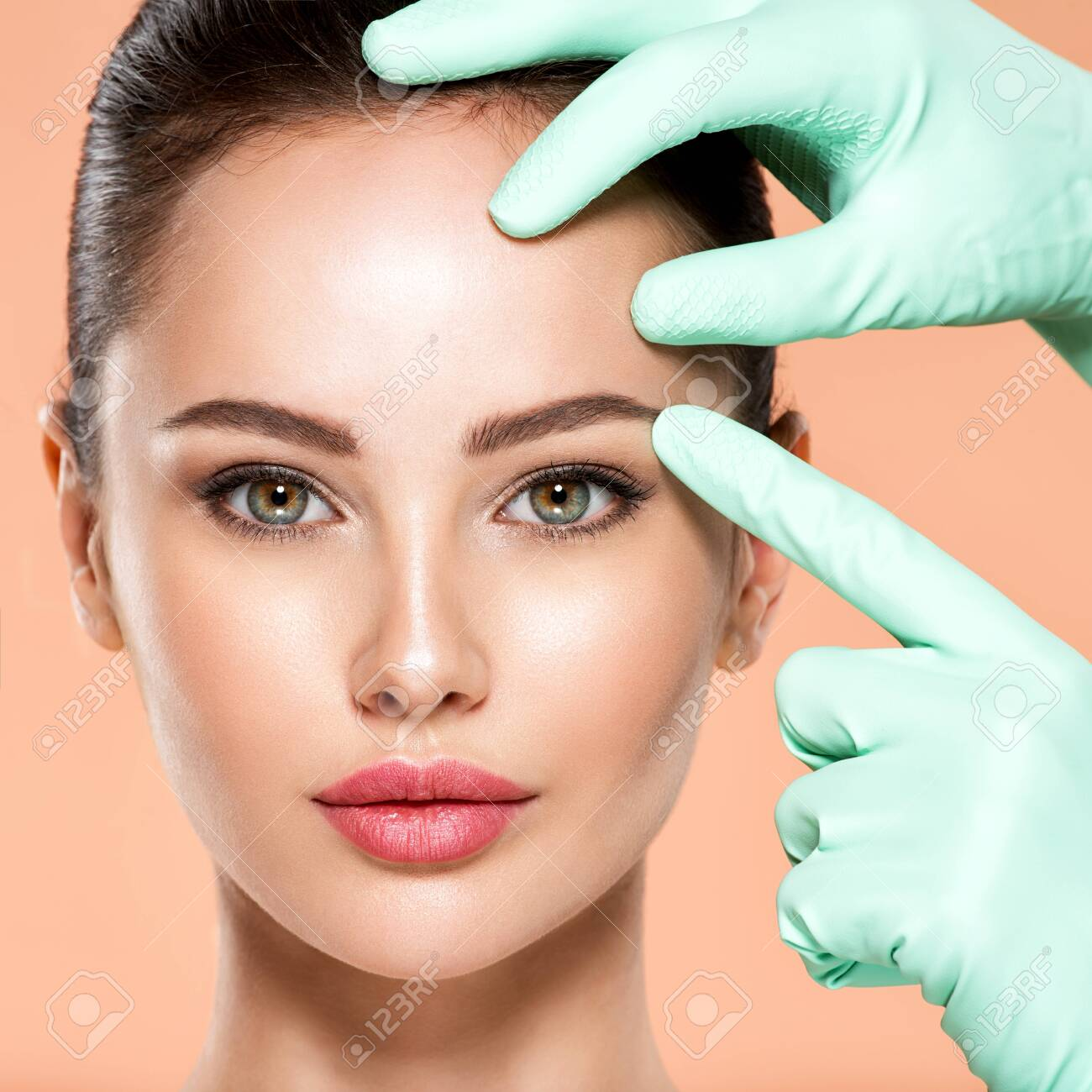 Face skin check before plastic surgery. Beautician touching young woman face. Doctor in medicine gloves checks a skin before plastic surgery. Beauty treatments. Colorful image - 155080021