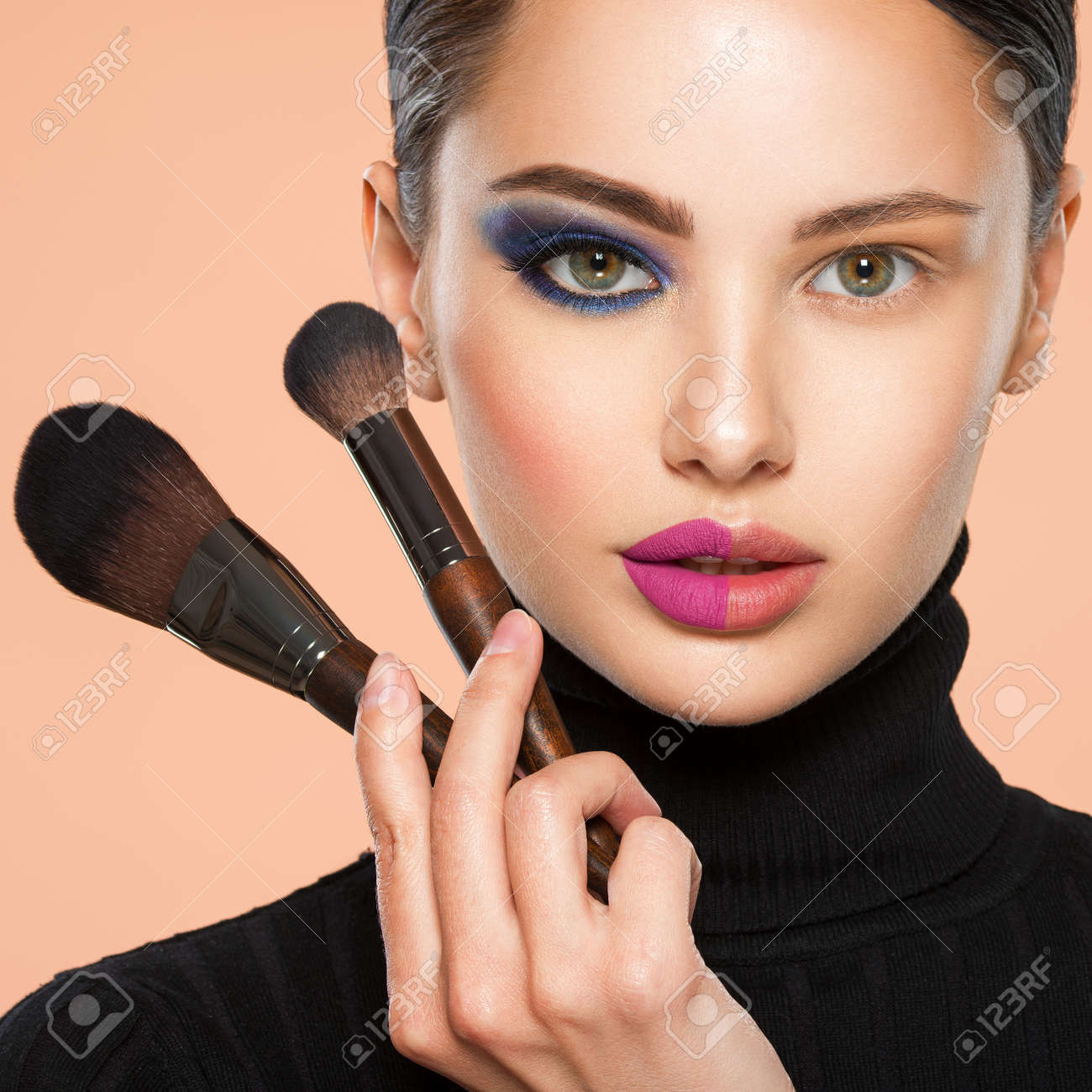 Portrait of a girl with cosmetic brush near face. Woman making makeup on the face using makeup brush. One half face of a beautiful white woman with bright makeup and the other is natural. - 156354415