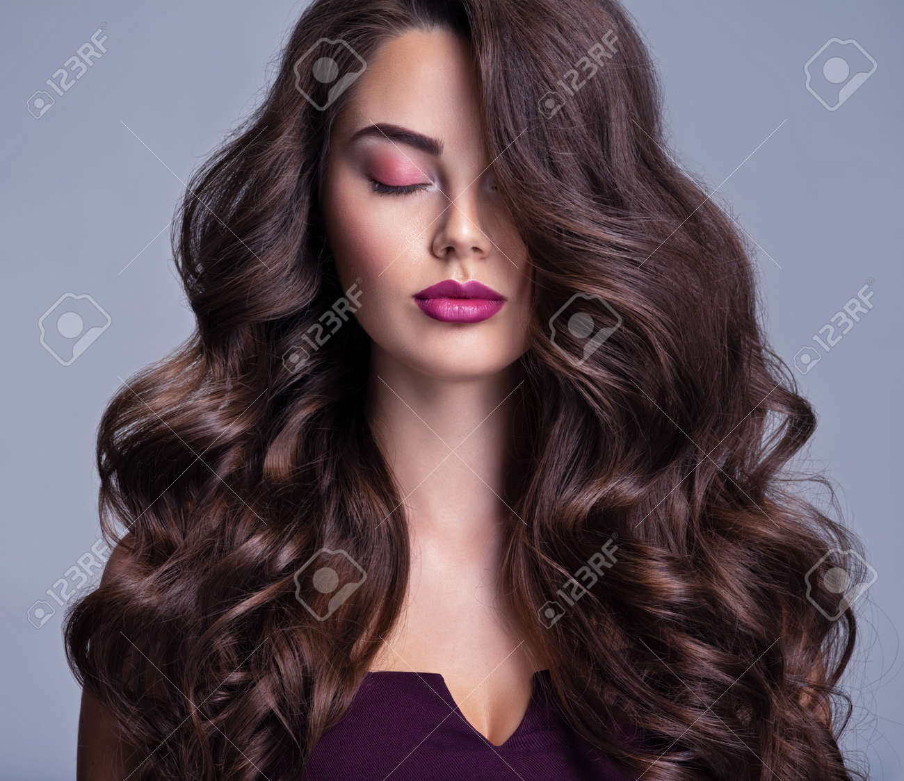 Fashion model with wavy hairstyle. Attractive young girl with curly hair posing at studio. Face of a beautiful woman with long brown curly hair. Female face with purple makeup. Violet make-up. - 156608385