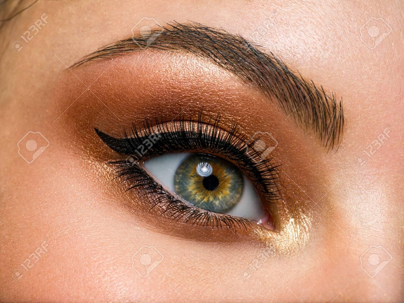 Beautiful female eye with brown, shiny makeup. Fashionable brown makeup. Macro image of a woman's eye. - 156777832