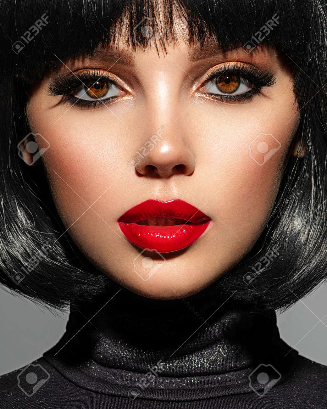 Beautiful brunette girl with red lips and black bob hairstyle. Pretty young woman with black hair. Closeup portrait of a model with bright makeup on a face. Fashion portrait of a pretty lady. - 166421654