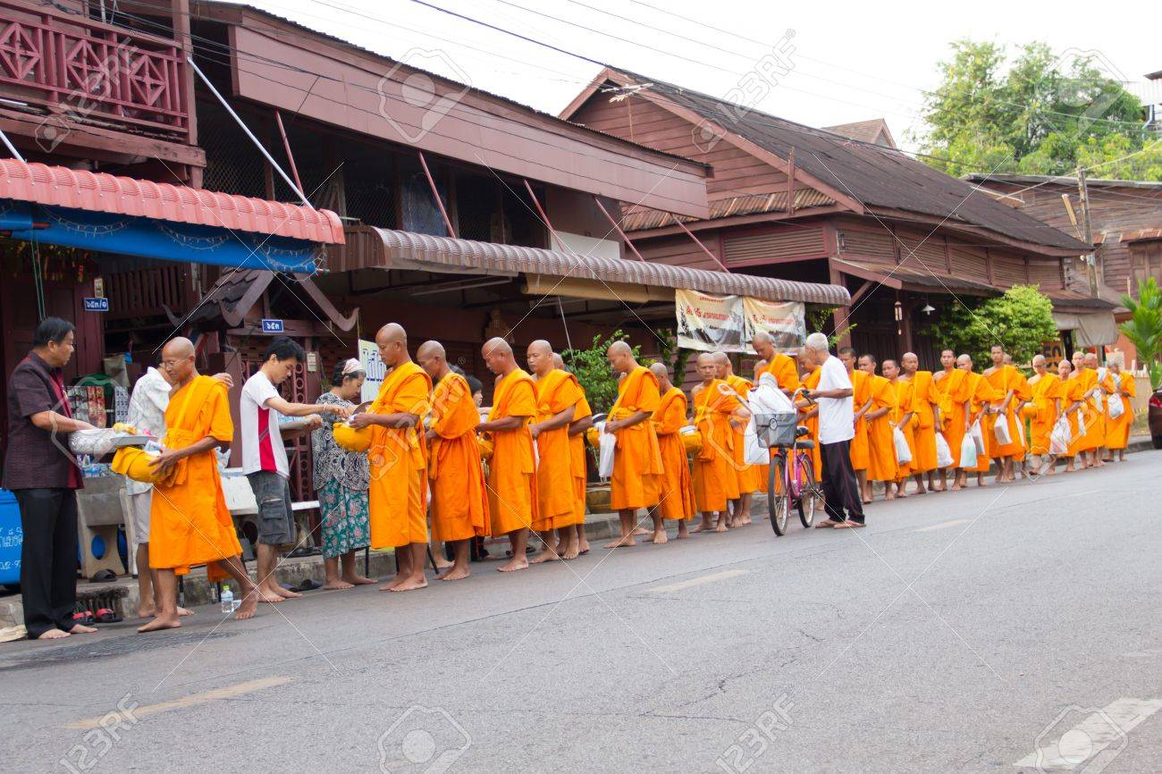 SAKONNAKHON , THAILAND - October 30:unidentified people give food offerings to Buddhist monks on October 30, 2012 in Sakonnakhon, Thailand. Thai traditional, people will make merit making by give food to monk Stock Photo - 16768957