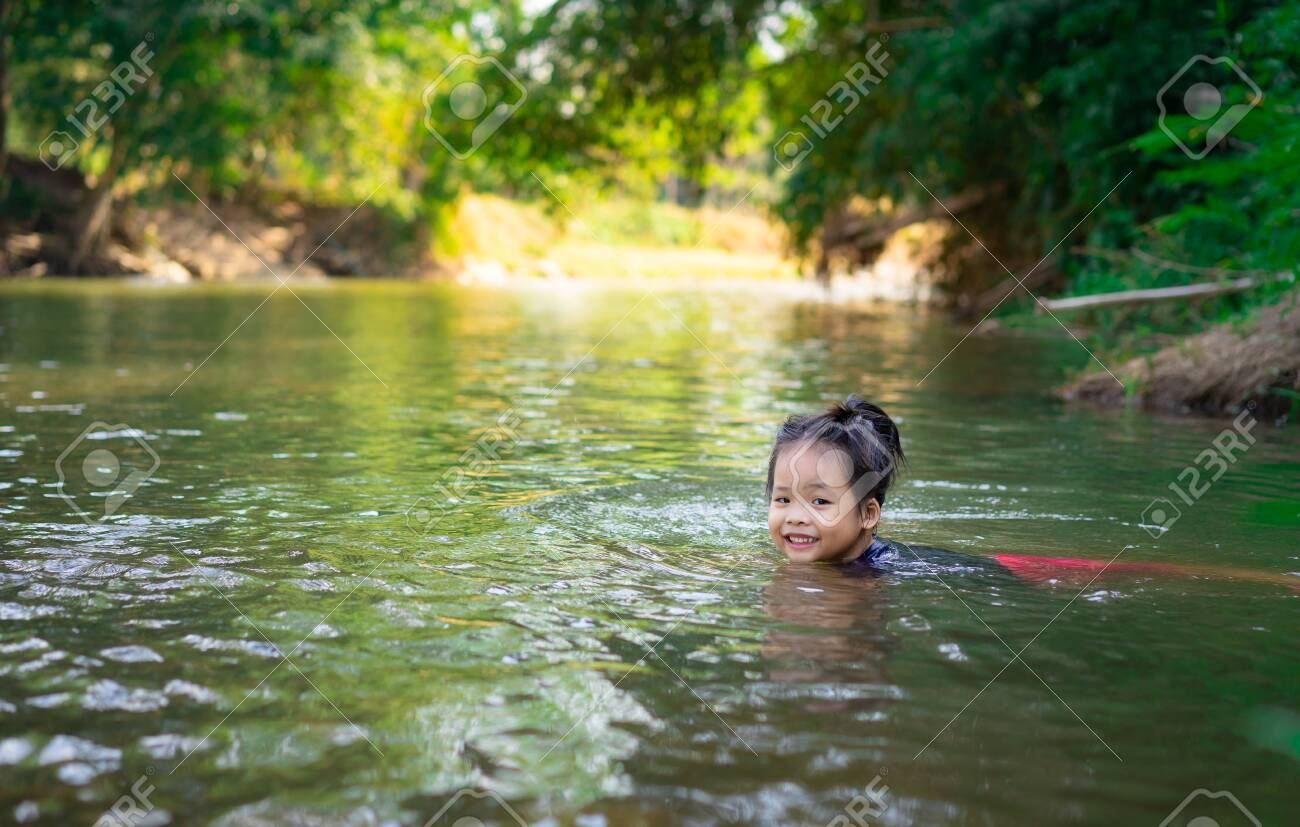 little asian girl playing in the river with sunlight - 129913958