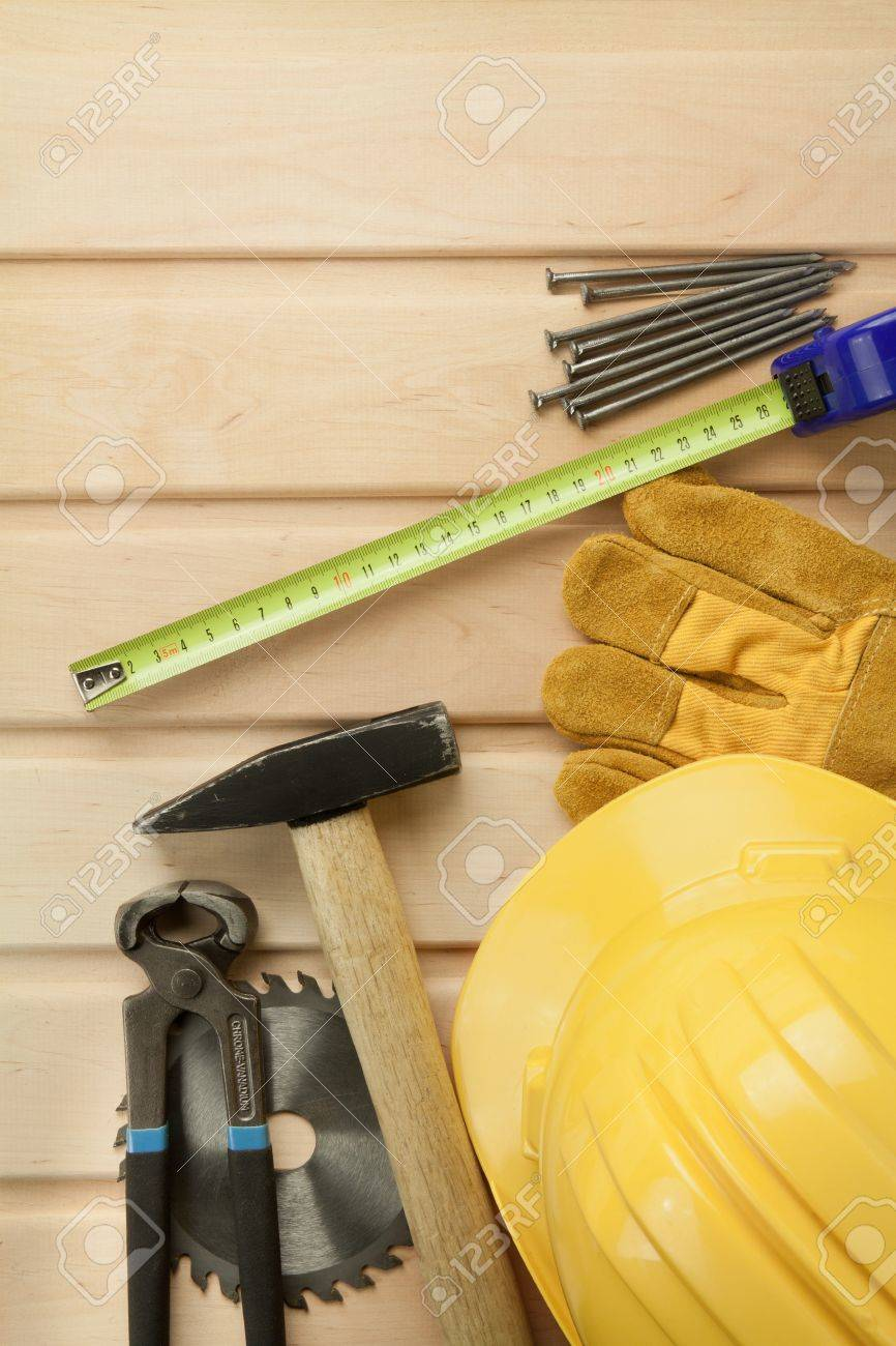 Working tools on a wooden boards background. Including saw, ruler, helmet, nails, pliers,hammer. Stock Photo - 9568871
