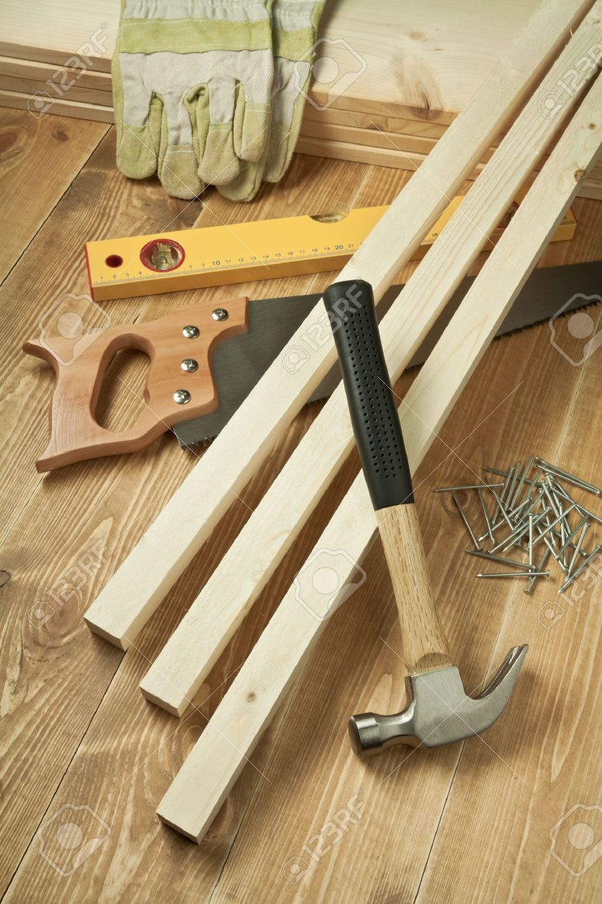 Hammer, saw, level, gloves, planks and nails on wooden floor Stock Photo - 9568982