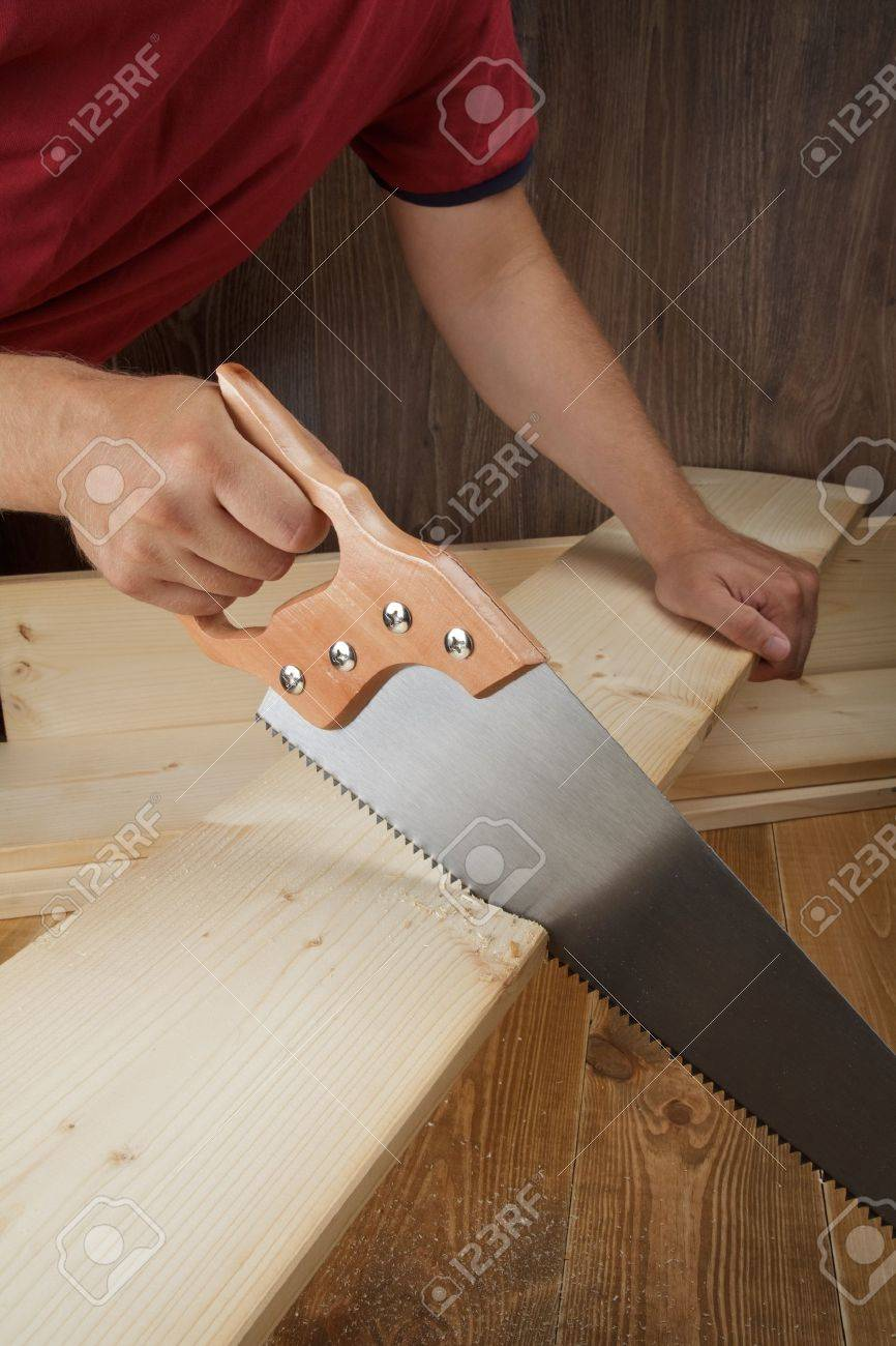 Wood workshop. Carpenter cutting plank with hand saw. Stock Photo - 10205070