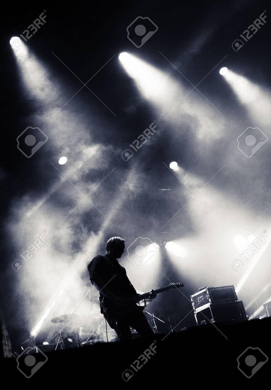Rock concert stage. Guitarist playing on electric guitar. Stock Photo - 32450650