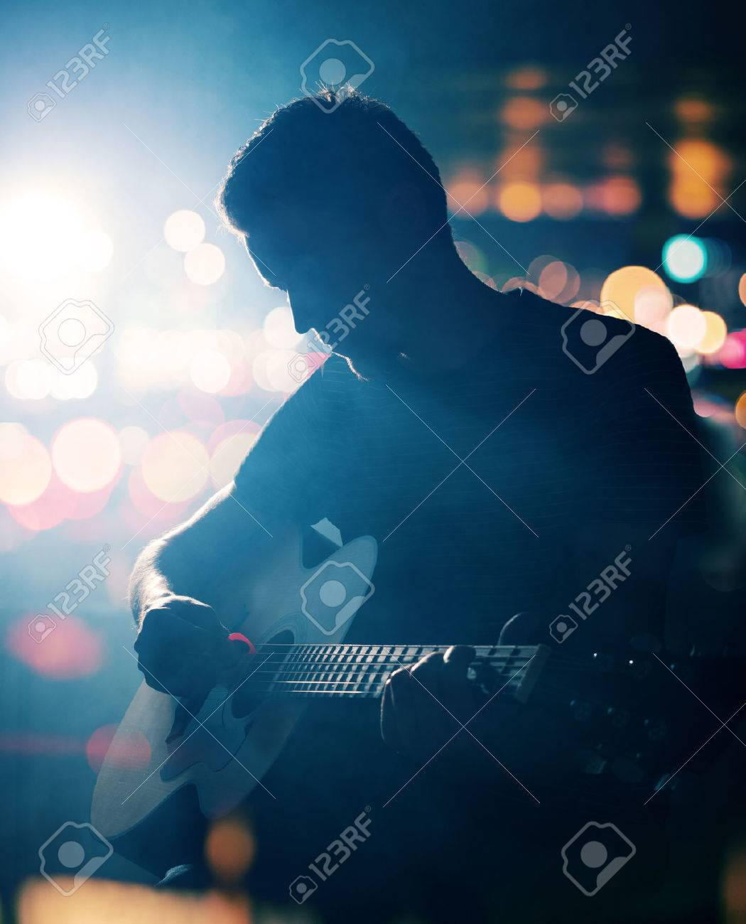 Guitarist playing acoustic guitar. Unplugged performance in the dark. Stock Photo - 34980660